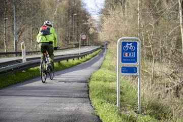 Man cycling on a route beside a road, with a barrier in between to separate them