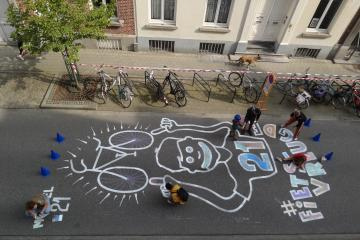 Children use chalk to draw on the street